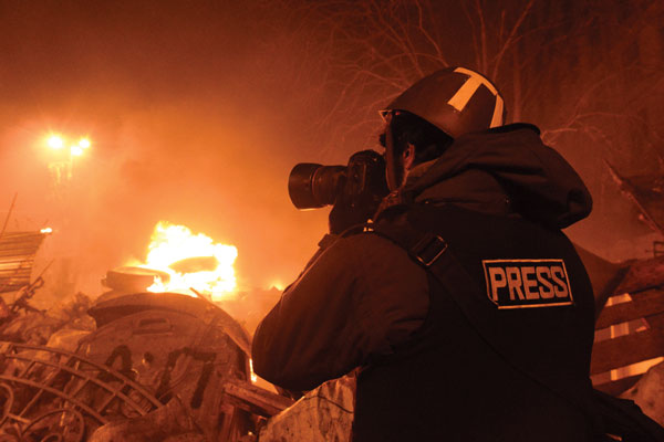 A Telling Witness Journalists' Commemorative Service photographer in flak jacket fire in background