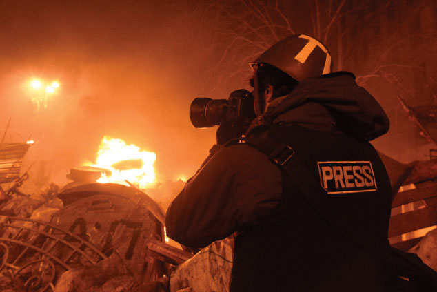Photographer wearing flak jacket with fire burning behind