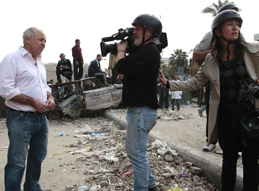 Jeremy Bowen in front of camera with nervous producer in war zone