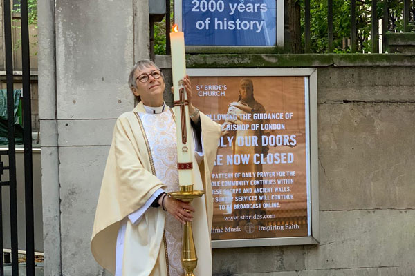 Rector Alison Joyce holding a candle in front of the closed gates of St Bride's